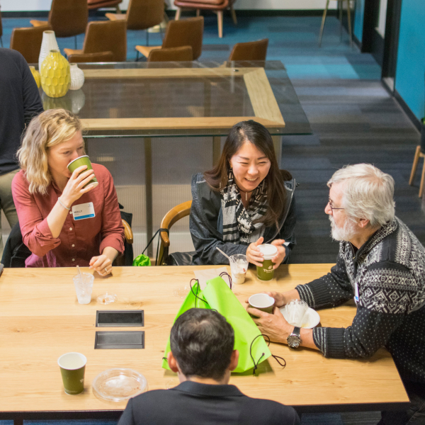 Two men and two women seated around a wooden table, drinking from paper cups and laughing together