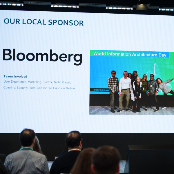 Screen showing the local sponsor, Bloomberg, and a photo of a group of people for World Information Architecture Day