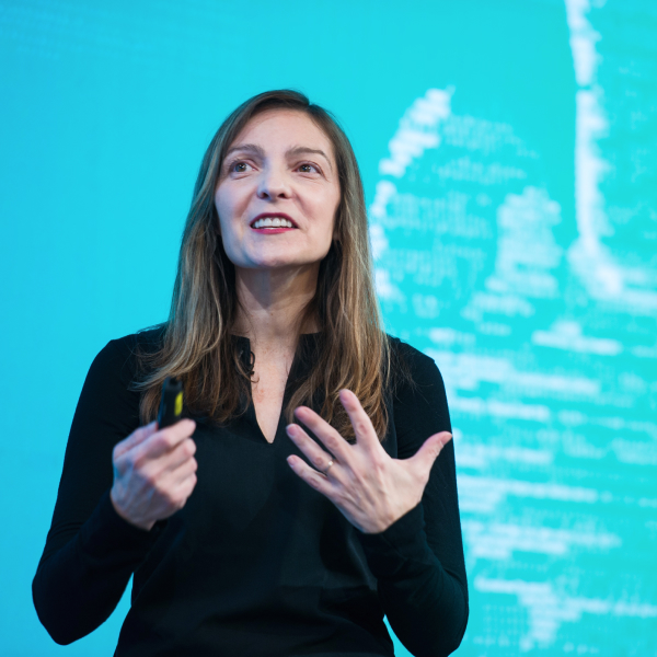 Woman smiling and speaking emphatically with her hands against a bright blue-green background