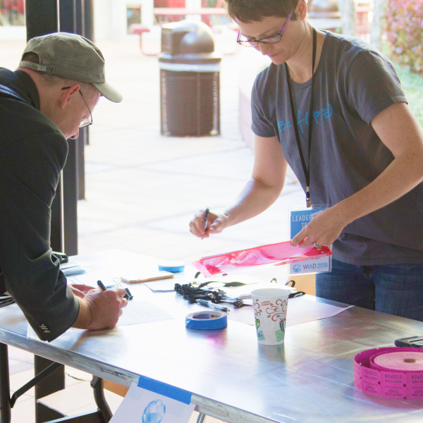 Woman volunteer helps man sign-up at World IA Day event table